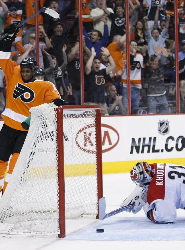 Philadelphia Flyers' Wayne Simmonds, left, reacts to scoring the Flyers' third goal against Carolina Hurricanes' Anton Khudobin, right, of Russia during the second period of an NHL hockey game, Sunday, April 13, 2014, in Philadelphia