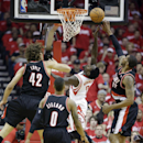 Houston Rockets' Patrick Beverley has a shot blocked as he drives against Portland Trail Blazers' LaMarcus Aldridge (12) and Robin Lopez (42) during the first half in Game 1 of an opening-round NBA basketball playoff series, Sunday, April 20, 2014, in Hou