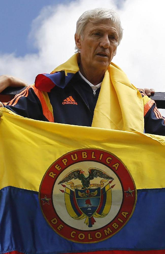 In this July 6, 2014 file photo, Colombia's coach Jose Pekerman, from Argentina, holds a Colombian flag as the team parades before supporters as they are welcomed home from the World Cup, in Bogota, Colombia, following their loss to Brazil in the quarterfinals. Colombia's Football Federation announced on Tuesday, Aug. 19, 2014 that Pekerman will stay on as coach for the national selection