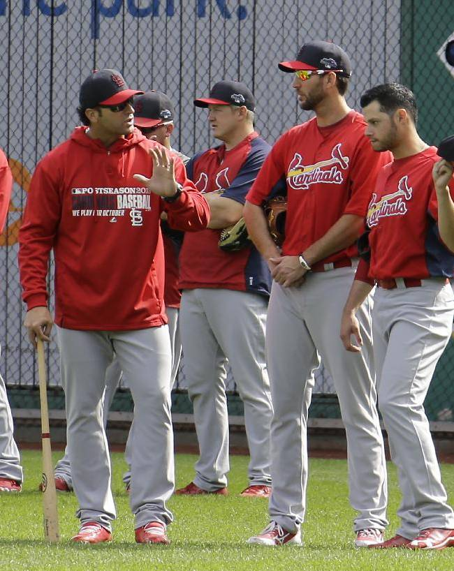 St. Louis Cardinals manager Mike Matheny, center left, talks with pitchers Adam Wainwright, center right, Joe Kelly, right, in the outfield as the team takes batting practice before Game 4 of a National League division baseball series against the Pittsburgh Pirates on Monday, Oct. 7, 2013 in  Pittsburgh
