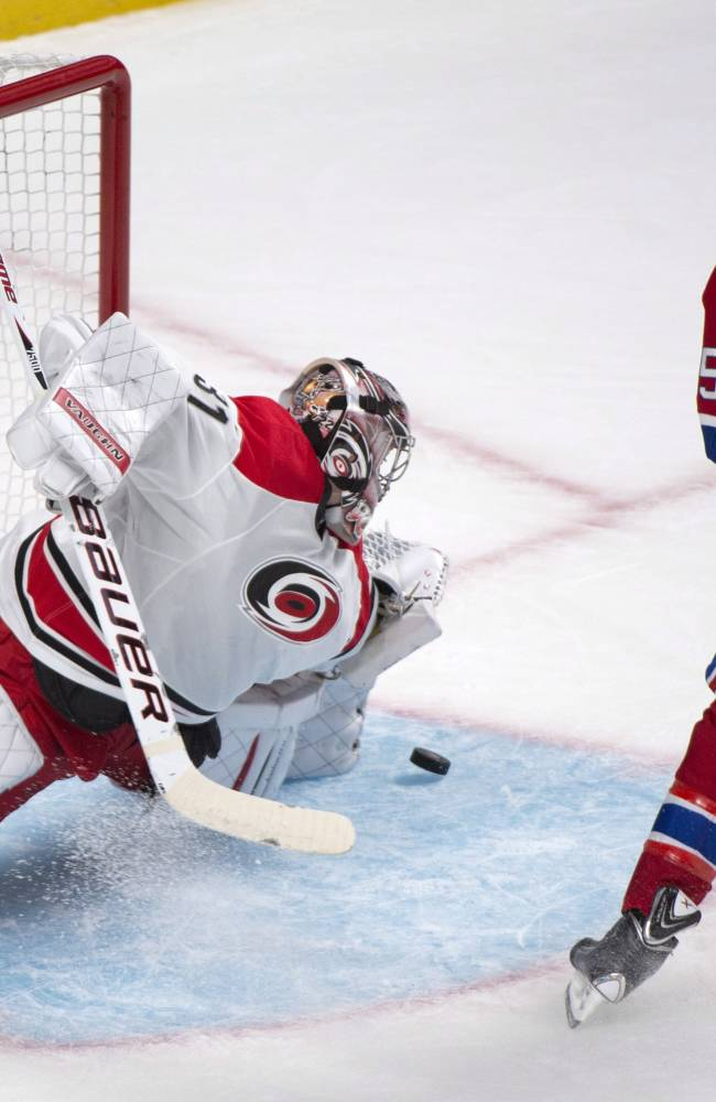 Carolina Hurricanes goaltender Anton Khudobin, left, makes a save against Montreal Canadiens' Michael Blunden during the first period of a preseason NHL hockey game Saturday, Sept. 21, 2013, in Montreal