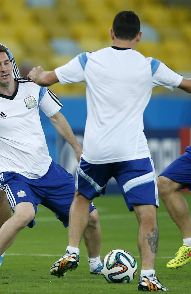 From left, Argentina's Sergio Aguero, Lionel Messi, Maxi Rodriguez, and Javier Mascherano pass the ball during a training session at the Maracana Stadium in Rio de Janeiro, Brazil, Saturday, June, 14, 2014. Argentina will face  Bosnia-Herzegovina in group F of the 2014 soccer World Cup at the stadium on Sunday