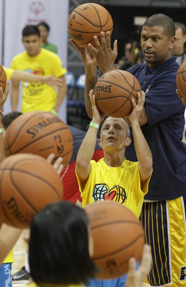 Indiana Pacers' Ian Mahinmi, right, and former NBA basketball player Jalen Rose, second from right, conduct a basketball clinic for Filipino Special Olympics athletes Wednesday, Oct. 9, 2013, at the Mall of Asia Arena in Pasay city, south of Manila, Philippines. The Indiana Pacers will play against the Houston Rockets on Thursday in the first NBA game in this basketball-obsessed Southeast Asian nation, part of the NBA's global schedule that will have eight teams play in six countries this month