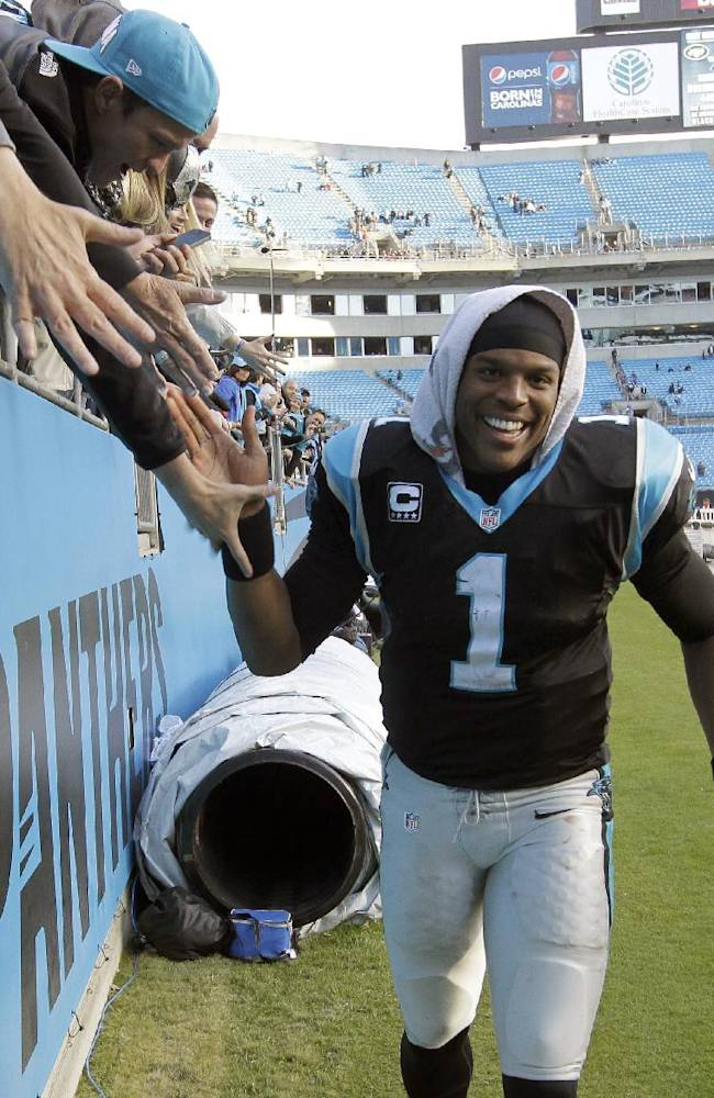Carolina Panthers' Cam Newton (1) gives high fives to fans after an NFL football game in Charlotte, N.C., Sunday, Dec. 1, 2013. The Panthers won 27-6