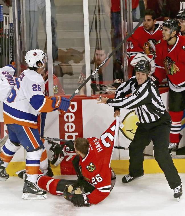 Linesman Brad Kovachik pulls Chicago Blackhawks' Michal Handzus away from New York Islanders' John Tavares as Islanders' Matt Moulson gets into a shouting match with Chicago Blackhawks' Marcus Kruger late in the third period as the Blackhawks defeated the Islanders 3-2 in an NHL game in Chicago on Friday, Oct. 11, 2013