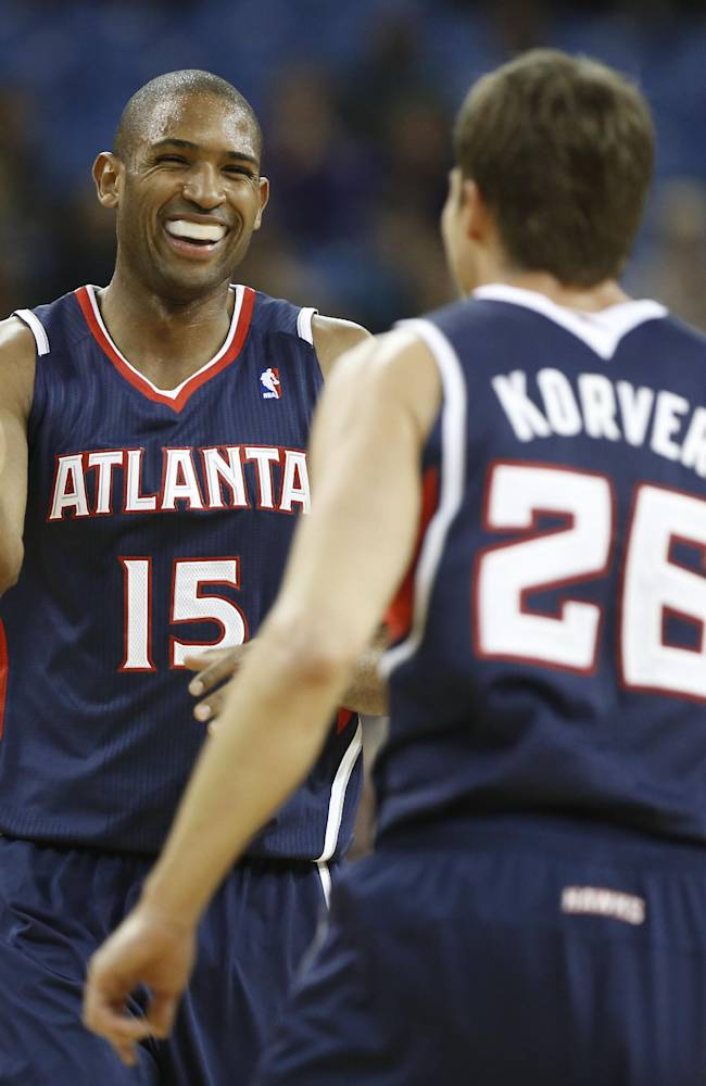Atlanta Hawks center Al Horford, left, smiles as he receives congratulations from teammate Kyle Korver after scoring during the  fourth quarter against the Sacramento Kings in a NBA basketball game in Sacramento, Calif., Tuesday, Nov. 5, 2013.  The Hawks won 105-100