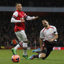 Liverpool's Luis Suarez, right, is tackled by Arsenal's Alex Oxlade-Chamberlain during their English FA Cup fifth round soccer match at Emirates Stadium in London, Sunday, Feb. 16, 2014