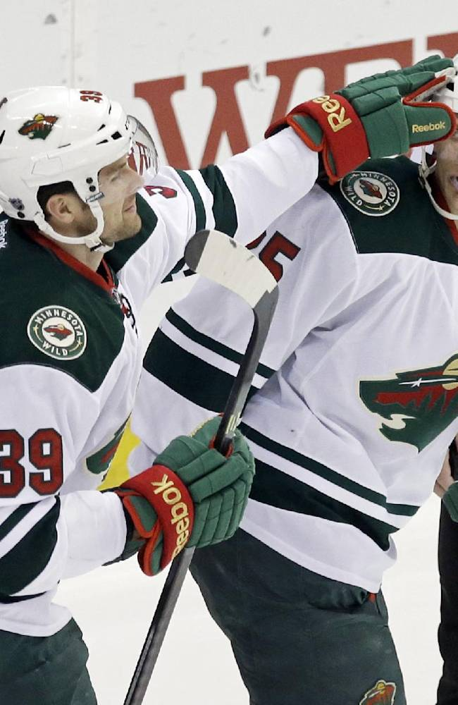 Minnesota Wild's Nate Prosser, left, gives a tap on the helmet to Minnesota Wild's Jonas Brodin of Sweden after Brodin scored against Nashville Predators goalie Carter Hutton in the first period of an NHL hockey game, Thursday, Feb. 6, 2014, in St. Paul, Minn