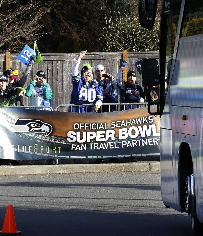 Fans cheer as buses carrying Seattle Seahawks players and coaches leave team headquarters in Renton, Wash., Sunday, Jan. 26, 2014. The Seahawks were heading to the airport for their flight east  to play the Denver Broncos in the NFL Super Bowl XLVIII football game in East Rutherford, N.J