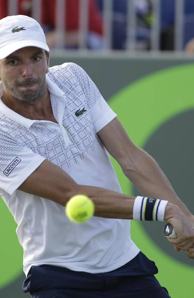Julien Benneteau, of France, returns the ball to Ernests Gulbis, of Latvia, during the Sony Open tennis tournament, Friday, March 21, 2014, in Key Biscayne, Fla