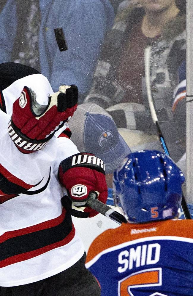 New Jersey Devils' Michael Ryder (17) grabs the puck out of the air as Edmonton Oilers' Ladislav Smid (5) tries to knock it down with his stick during the first period of an NHL hockey game Monday, Oct. 7, 2013, in Edmonton, Alberta