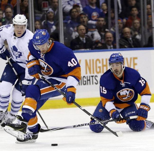 New York Islanders' Cal Clutterbuck (15) passes the puck to teammate Michael Grabner (40) as Toronto Maple Leafs' Jake Gardiner (51) watches during the second period of an NHL hockey game Thursday, Feb. 27, 2014, in Uniondale, N.Y