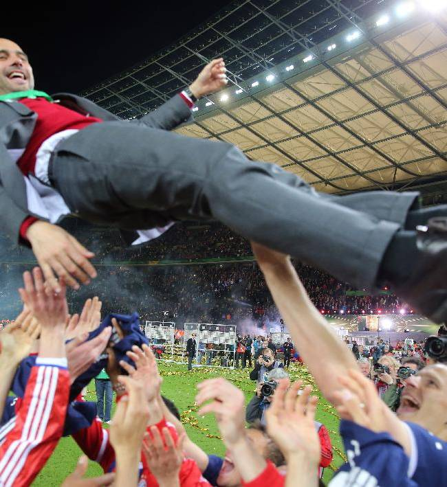 TIn this picture taken Saturday May 17, 2014, the Bayern Munich soccer team celebrate with head coach Pep Guardiola after they won the German soccer cup final against Borussia Dortmund in Berlin