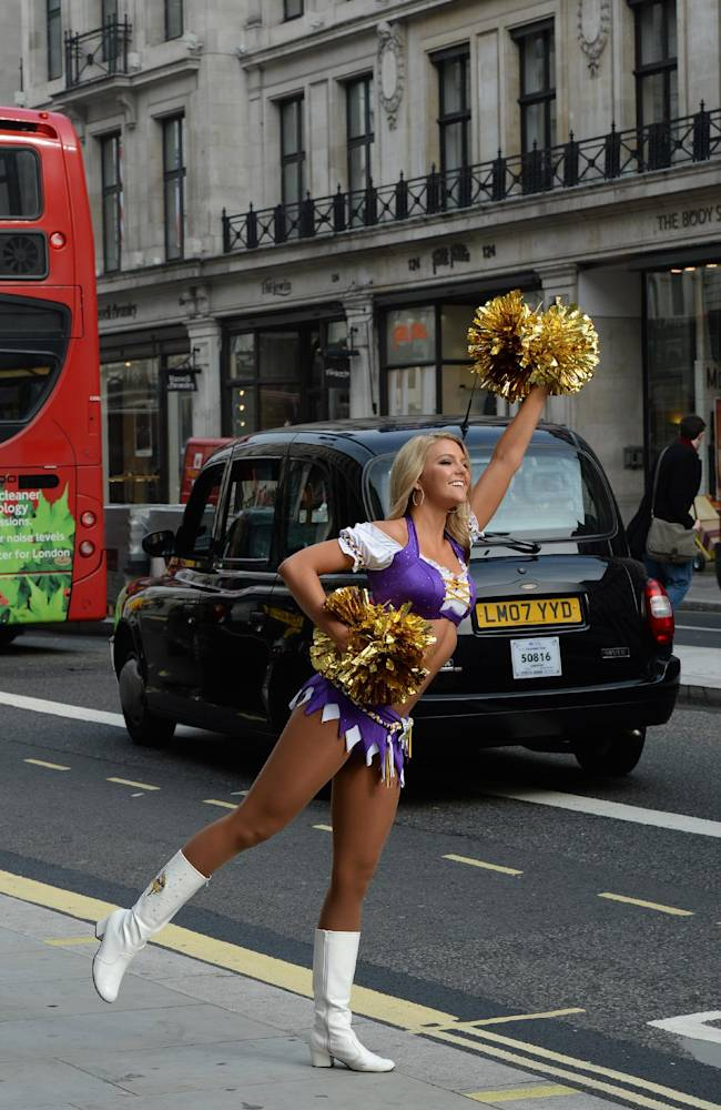 In this image made available by the NFL, a Minnesota Vikings cheerleader stands in London's Regent Street during an arranged photo shoot, Wednesday, Sept. 25, 2013. The Minnesota Vikings will play the Pittsburgh Steelers at London's Wembley Stadium on Sunday