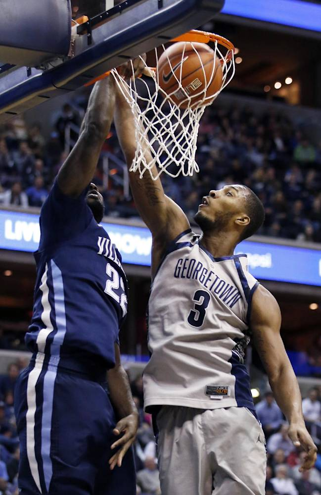 Villanova forward JayVaughn Pinkston, left, dunks the ball over Georgetown forward Mikael Hopkins (3) during the first half of an NCAA college basketball game, Monday, Jan. 27, 2014, in Washington