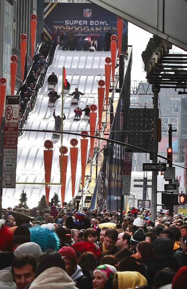 Football fans experience the 60-feet tall toboggan run on Super Bowl Boulevard, 13 blocks of entertainment activity stretching from 47th Street to 34th Street, Saturday Feb. 1, 2014, in New York