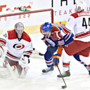 Carolina Hurricanes goalie Cam Ward (30) makes the save as Hurricanes' Jay Harrison (44) and Edmonton Oilers' Luke Gazdic (20) look for the rebound during second period NHL hockey action in Edmonton, Alberta, on Tuesday, Dec. 10, 2013 The Associated Press