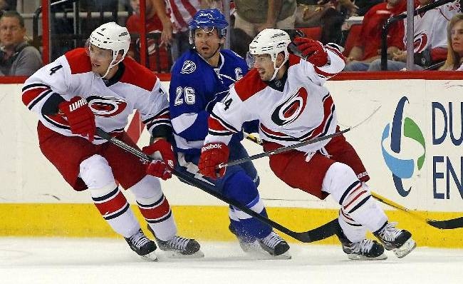 Tampa Bay Lightning's Martin St. Louis (26) is flanked by Carolina Hurricanes' Nathan Gerbe (14), and Andrej Sekera (4) of Slovakia, during the second period of an NHL hockey game in Raleigh, N.C., Friday, Nov. 1, 2013. Lightning won 3-0