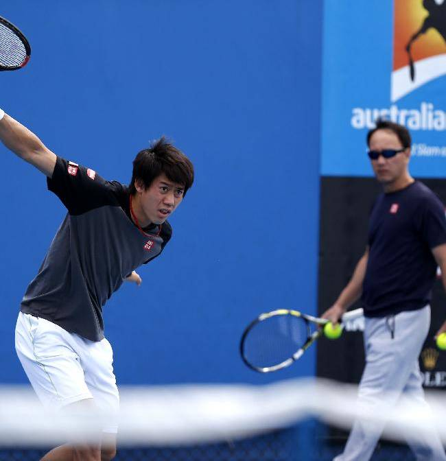 Kei Nishikori of Japan, left,  works out with his coach Michael Chang ahead of his quarterfinal against Stan Wawrinka of Switzerland at the Australian Open tennis championship in Melbourne, Australia, Wednesday, Jan. 28, 2015