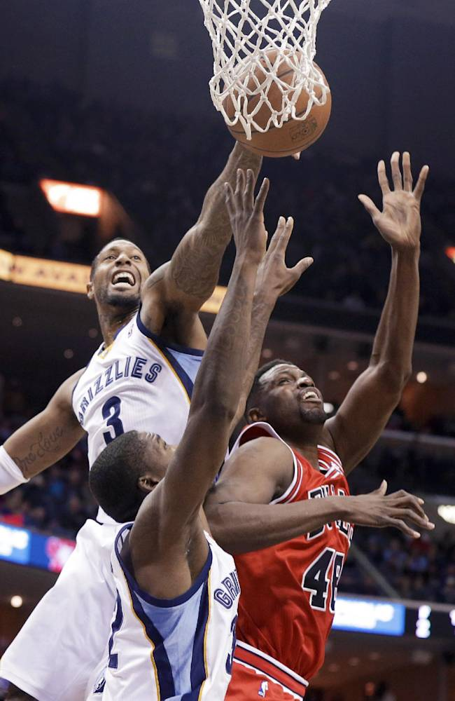Memphis Grizzlies' James Johnson (3), Ed Davis, center, and Chicago Bulls' Nazr Mohammed, right, go for a rebound in the first half of an NBA basketball game in Memphis, Tenn., Monday, Dec. 30, 2013