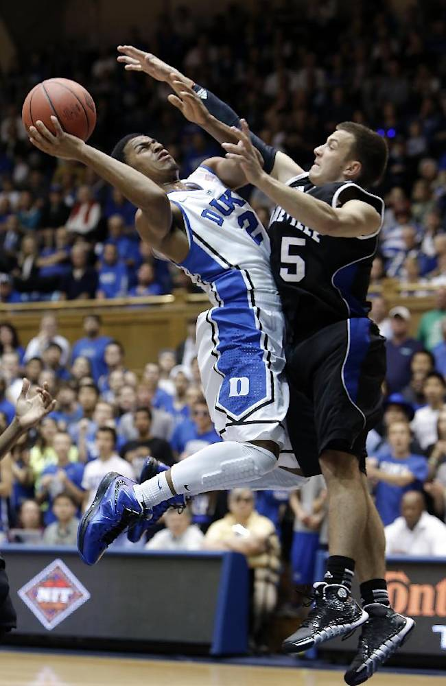 Duke's Quinn Cook drives to the basket against UNC-Asheville's Andrew Rowsey during the first half of an NCAA college basketball game in Durham, N.C., Monday Nov. 18, 2013