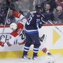 Winnipeg Jets' Dustin Byfuglien (33) dumps Carolina Hurricanes' Riley Nash (20) during the first period of an NHL hockey game, Saturday, March 22, 2014, in Winnipeg, Manitoba The Associated Press