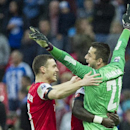 Arsenal's Thomas Vermaelen celebrates with Lukasz Fabianski, at the end of their English FA Cup semifinal soccer match against Wigan Athletic, at the Wembley Stadium in London, Saturday, April 12, 2014