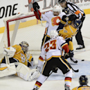 Calgary Flames right wing Devin Setoguchi (22) battles with Nashville Predators defenseman Anton Volchenkov (20) as the puck rolls past of Predators goalie Pekka Rinne (35) in the third period of an NHL hockey game Tuesday, Oct. 14, 2014, in Nashville, Te