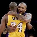 Phoenix Suns forward P.J. Tucker, right, hugs Los Angeles Lakers guard Kobe Bryant after an NBA basketball game in Los Angeles, Tuesday, Dec. 10, 2013 The Associated Press