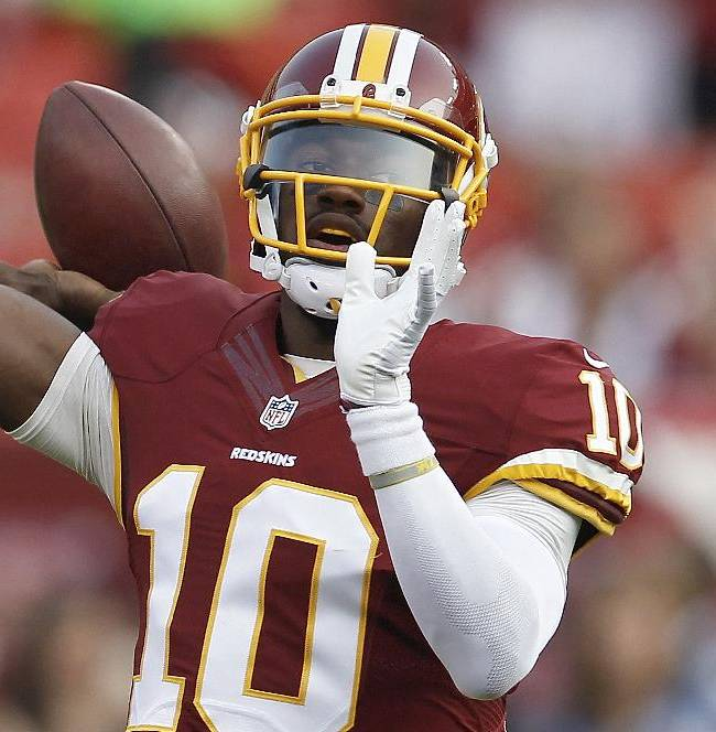 Washington Redskins quarterback Robert Griffin III warms up before an NFL football preseason game against the New England Patriots in Landover, Md., Thursday, Aug. 7, 2014