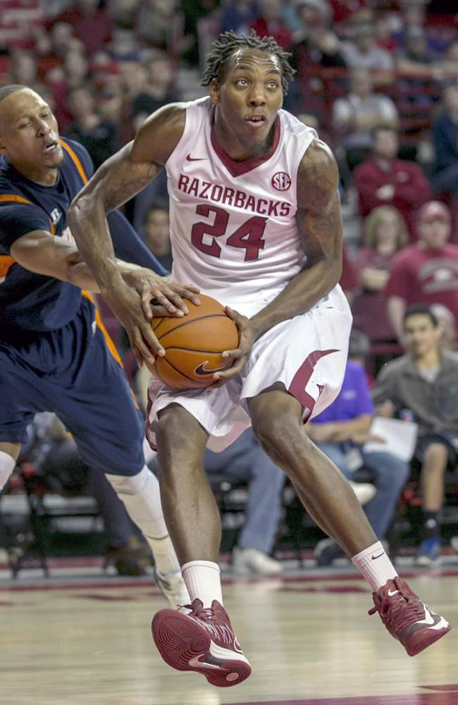 In this Dec. 19, 2013, filephoto, Arkansas' Michael Qualls (24) looks to the basket as Tennessee-Martin's Terence Smith attempts a steal during the second half of an NCAA college basketball game in Fayetteville, Ark. Qualls led Arkansas in its nonconference schedule but has struggled in Southeastern Conference play