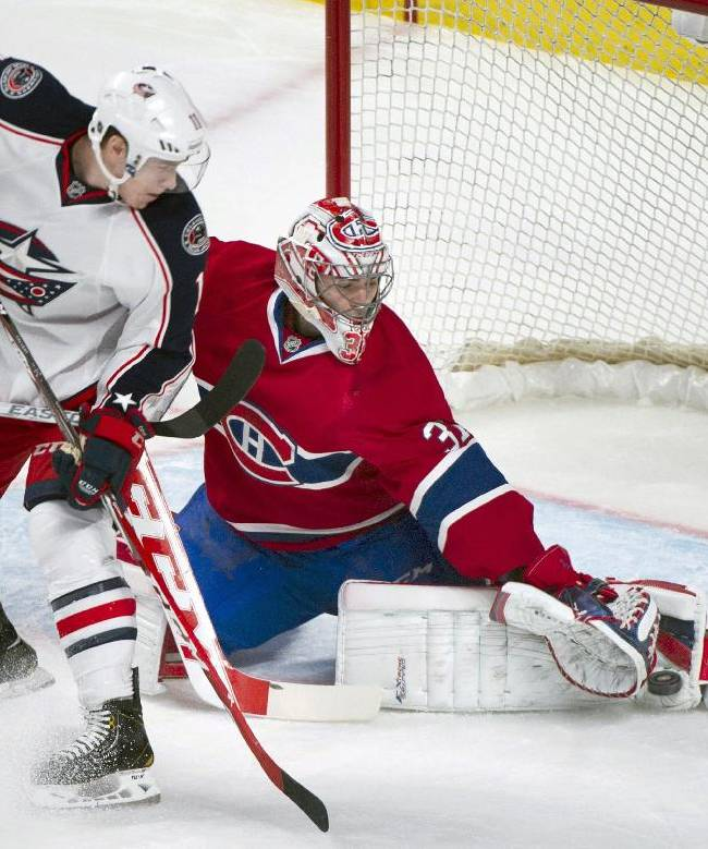 Montreal Canadiens goaltender Carey Price, right, makes a save against Columbus Blue Jackets' Matt Calvert during the first period of an NHL hockey game in Montreal, Thursday, March 20, 2014