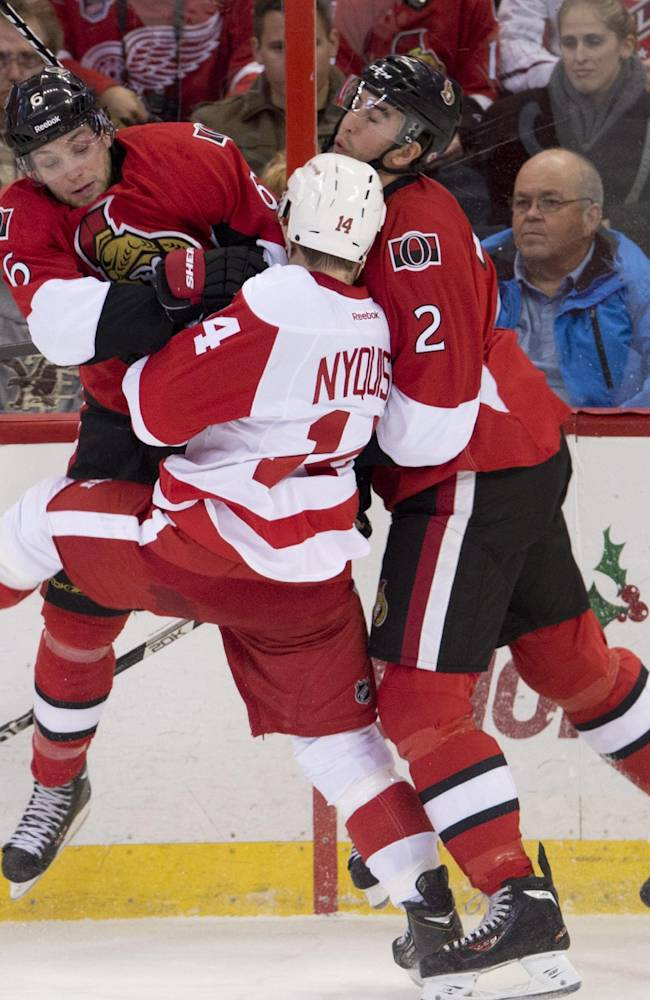 Ottawa Senators right wing Bobby Ryan, left, and defenseman Jared Cowen collide with Detroit Red Wings center Gustav Nyquist, center, during first period NHL action Sunday Dec. 1, 2013 in Ottawa, Ont