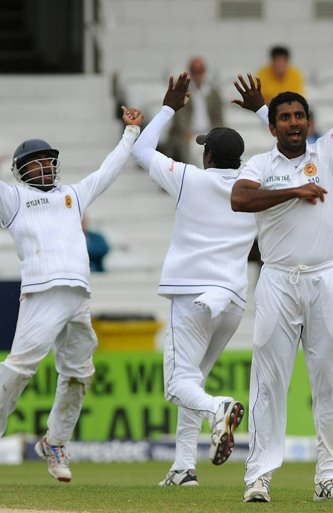 Sri Lanka's Dhammika Prasad, right, celebrates after bowling England's Matt Prior, caught by Kaushal Silva, left, for 10 runs, during day five of the Second Test Match between England and Sri Lanka at Headingley cricket ground, Leeds, England, Tuesday, June 24, 2014