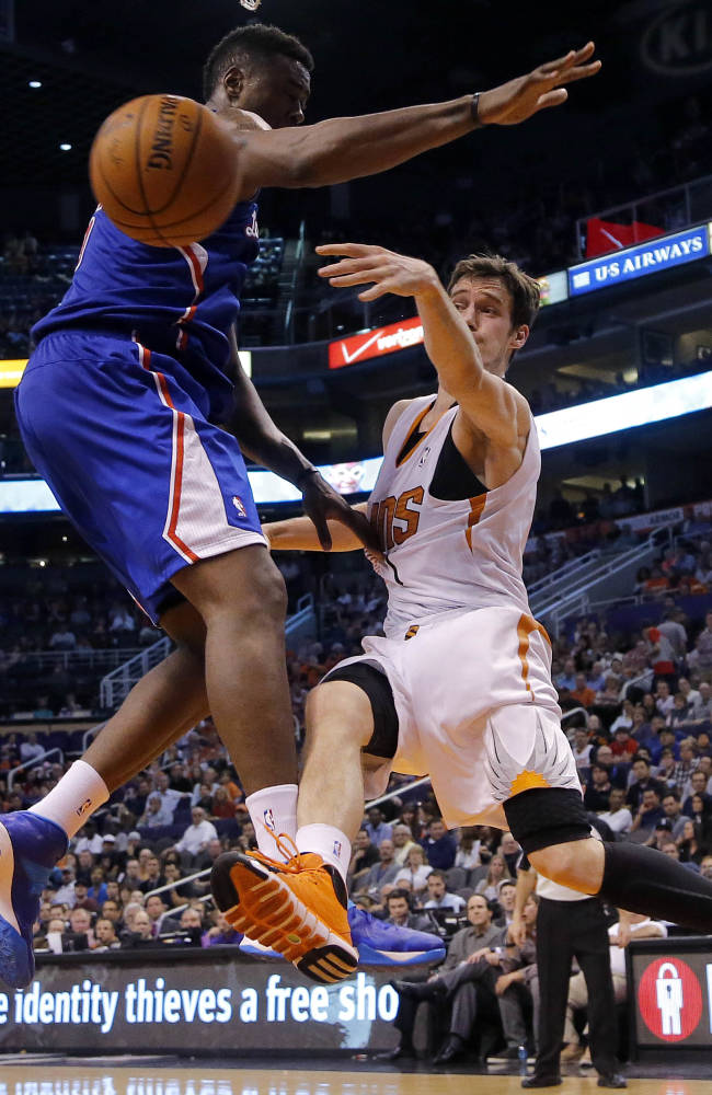 Phoenix Suns' Goran Dragic, of Slovenia, right, passes around Los Angeles Clippers' DeAndre Jordan during the second half of an NBA basketball game, Tuesday, March 4, 2014, in Phoenix
