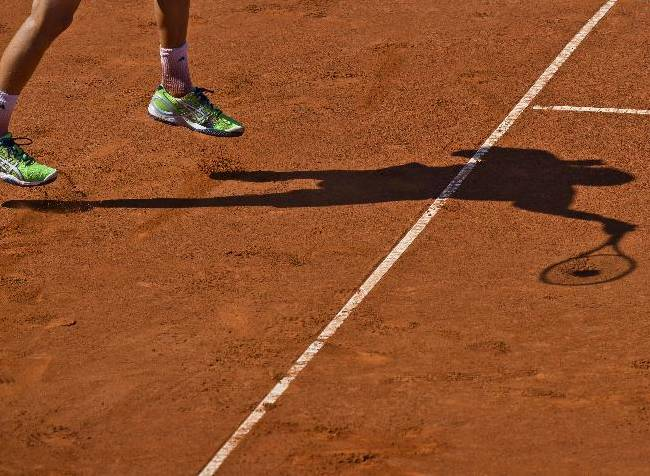Sweden's Christian Lindell casts a shadow as he returns a ball to Romania's Adrian Ungur during the first tennis match of a first round Davis Cup play-off tie between Romania and Sweden in Bucharest, Romania, Friday, Sept. 12, 2014. Sweden took the lead after Christian Lindell defeated Adrian Ungur in three sets