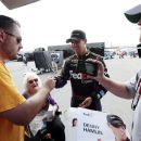 Denny Hamlin, center, signs autographs for fans after winning the pole for Sunday's NASCAR Sprint Cup Series auto race at Indianapolis Motor Speedway in Indianapolis, Saturday, July 28, 2012. (AP Photo/AJ Mast)