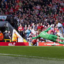 Liverpool's Raheem Sterling, right, scores past Manchester City's goalkeeper Joe Hart, center, during their English Premier League soccer match at Anfield Stadium, Liverpool, England, Sunday April 13, 2014