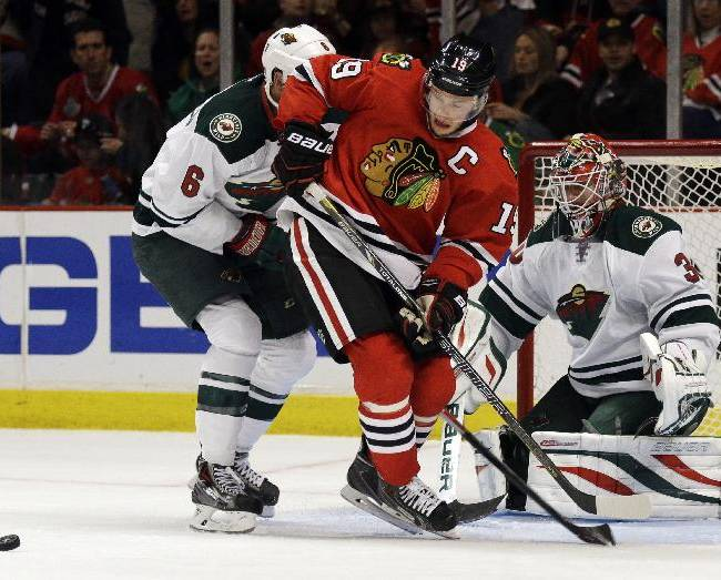 Chicago Blackhawks' Jonathan Toews (19) battles for the puck against Minnesota Wild's Marco Scandella (6) as goalie Ilya Bryzgalov (30) looks on during the second period in Game 2 of an NHL hockey second-round playoff series in Chicago, Sunday, May 4, 2014. The Blackhawks won 4-1