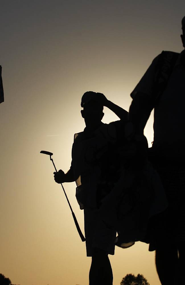 Golf players and caddies, seen in silhouette, leave the green of the 9th hole at the end of their first round of the Portugal Master golf tournament at the Victoria golf course in Vilamoura, southern Portugal, Thursday, Oct. 10, 2013