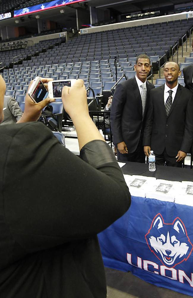 Connecicut coach Kevin Ollie, left, poses for a picture with player Ryan Boatright, DeAndre Daniels and Shabazz Napier at the American Athletic Conference NCAA college basketball media day on Wednesday, Oct. 16, 2013, in Memphis, Tenn