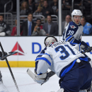 Los Angeles Kings center Jeff Carter, second from left, scores on Winnipeg Jets goalie Ondrej Pavelec, second from right, of the Czech Republic, as right wing Chris Thorburn, left, and defenseman Tobias Enstrom, of Sweden, look on during the second period