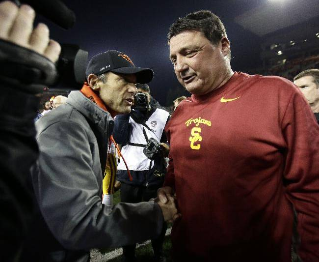 Southern California interim football coach Ed Orgeron, right, shakes hands with Oregon State coach Mike Riley after their NCAA college football game in Corvallis, Ore., Friday, Nov. 1, 2013. USC won 31-14
