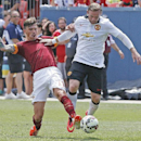 Manchester United's Wayne Rooney, right, and AS Roma's Alessio Romagnoli fight for control of the ball during an exhibition soccer match at Mile High Stadium in Denver, Saturday, July 26, 2014. Manchester United won 3-2