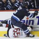 Winnipeg Jets' Mark Stuart (5) and Ottawa Senators' Erik Karlsson (65) crash into the boards during the second period of an NHL hockey game, Saturday, March 8, 2014 in Winnipeg, Manitoba. (AP Photo/The Canadian Press, John Woods)