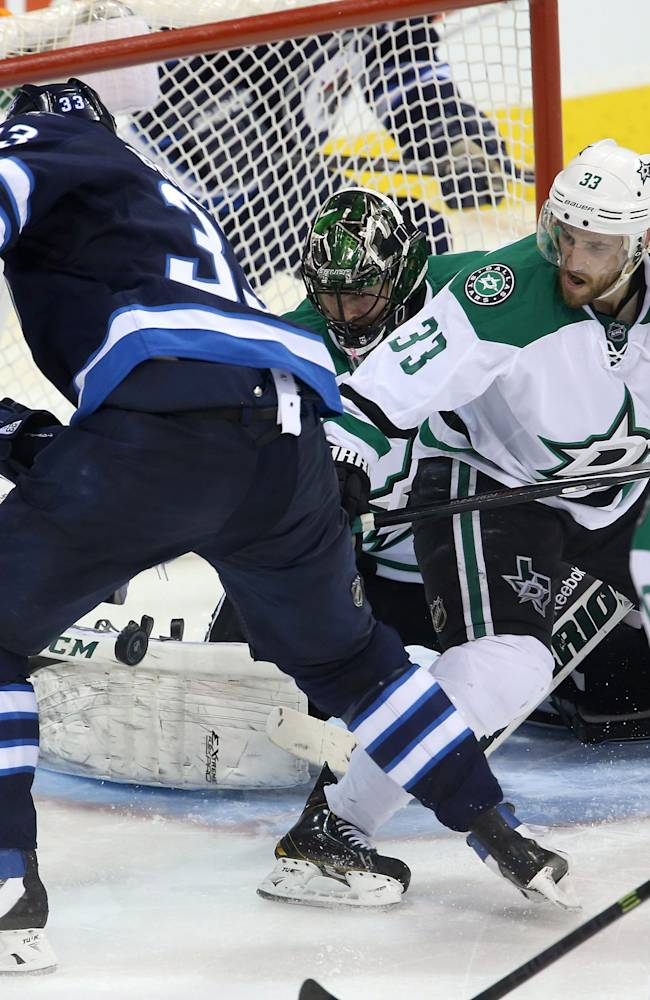 Winnipeg Jets' Dustin Byfuglien (33) scores his second goal of the game against Dallas Stars' goaltender Cristopher Nilstorp (42) with Alex Goligoski (33) in front of the net during third period NHL hockey action at MTS Centre in Winnipeg,  Manitoba, Sunday, March 16, 2014