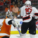 New Jersey Devils' Travis Zajac (19) is hit by a shot as Philadelphia Flyers' Rob Zepp (72) tries to defend during the third period of a preseason NHL hockey game, Thursday, Sept. 25, 2014, in Philadelphia. Philadelphia won 4-0. The Associated Press