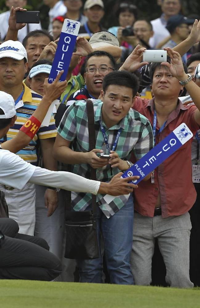 Chinese golf fans watch Tiger Woods of the United States and Rory Mcllory of Northern Ireland playing an exhibition golf match in Haikou, in southern China's island province Hainan, Monday, Oct. 28, 2013
