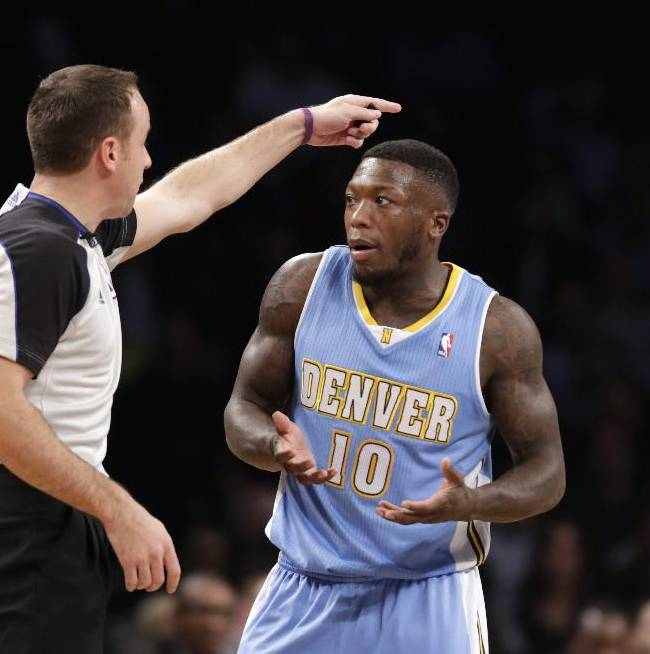 In this Dec. 3, 2013 file photo, Denver Nuggets point guard Nate Robinson (10) gestures as a referee tells him the ball goes to the Nets in the first half of an NBA basketball game against the Brooklyn Nets at the Barclays Center in New York. The NBA has fined Nuggets guard Robinson $25,000 for criticizing the officials following Denver's 97-95 victory over the Knicks last week