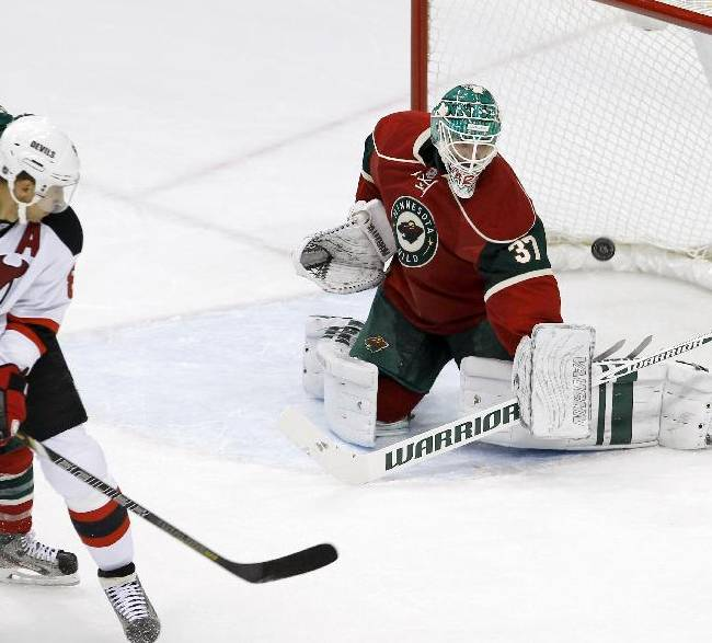 Minnesota Wild goalie Josh Harding (37) deflects a shot as New Jersey Devils right wing Dainius Zubrus, left, of Russia, watches during the first period of an NHL hockey game in St. Paul, Minn., Sunday, Nov. 3, 2013. The Wild won 4-0